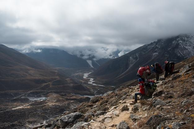 Porteiro nepalês carregando grandes cargas de sacos nas costas ao longo de uma trilha de lobuche para gok