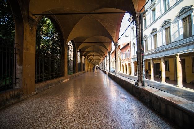 Pórtico de rua medieval com casas de cores vivas na cidade velha em um dia ensolarado, bolonha, emilia-romagna, itália