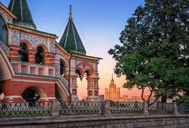 Pórtico ornamentado da catedral de são basílio em moscou e a casa na barragem de kotelnicheskaya na luz suave de uma noite