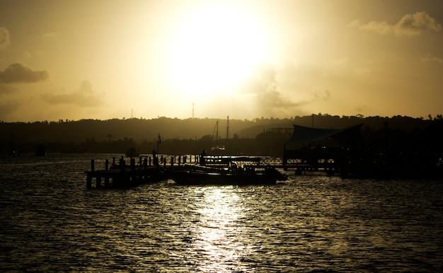 Porto comercial de barcos a motor no mar negro ao pôr do sol.