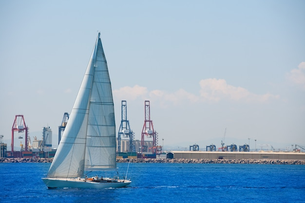 Porto da cidade de valência com veleiro e guindastes no fundo