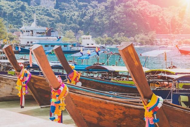Porto da ilha tropical com barcos de cauda longa de madeira atracados de táxi doméstico e montanhas de pescadores