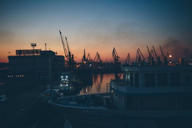 Porto de embarque antigo e navio velho. luzes da noite