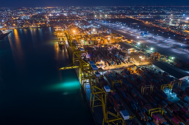 Porto de embarque e carga de contêineres à vista aérea noturna