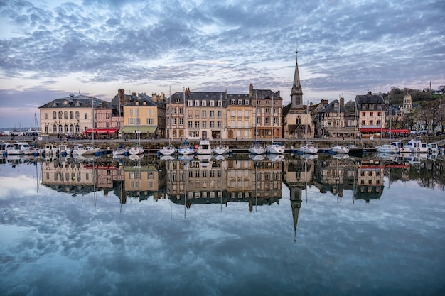 Porto de honfleur com os edifícios refletindo na água sob um céu nublado na frança