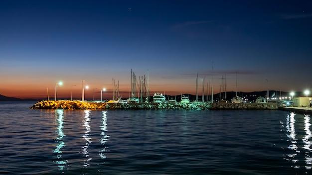Porto marítimo à noite na costa do mar egeu com vários barcos atracados, postes de luz na grécia
