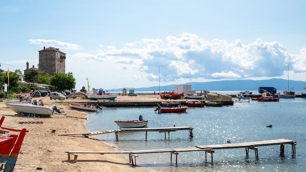 Porto marítimo, barcos atracados no mar egeu, poucos carros estacionados, dois pequenos cais de madeira e torre de prosphorion, ouranoupolis, grécia