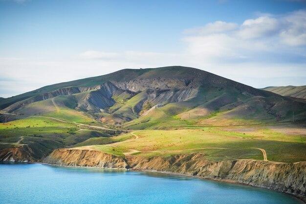 Porto marítimo com água azul, campo verde e céu azul com nuvens