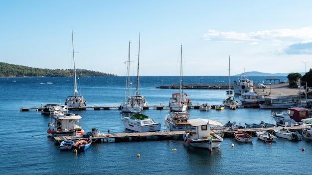 Porto marítimo do egeu com vários iates e barcos atracados, cais de madeira, tempo bom em neos marmaras, grécia