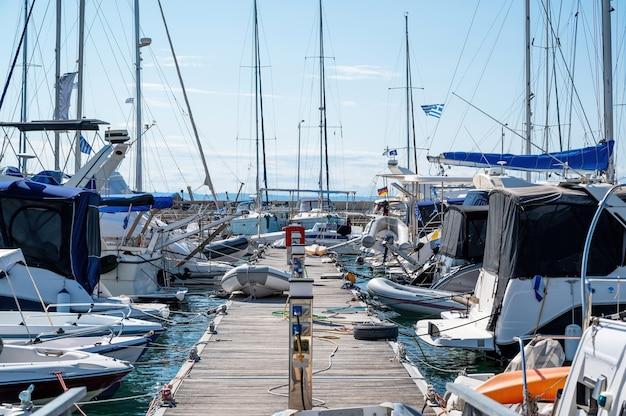 Porto marítimo do egeu com vários iates e barcos atracados, píer de madeira, tempo claro em nikiti, grécia