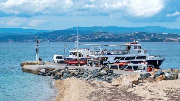 Porto marítimo, vários barcos atracados no mar egeu, dois carros estacionados em um píer em ouranoupolis, grécia