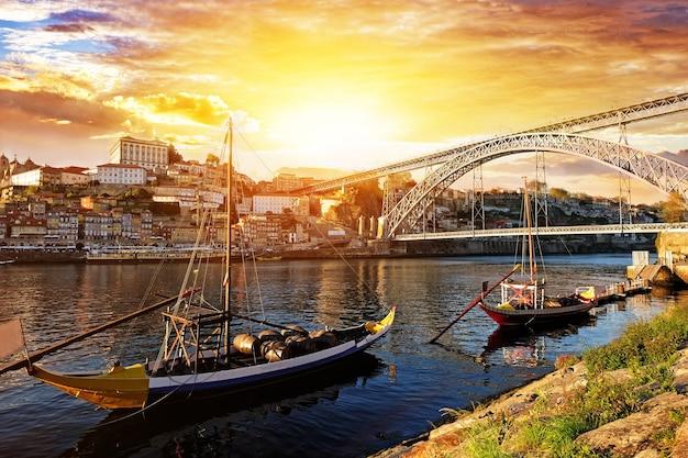 Porto, portugal, ponte dom luis e barcos no rio douro. lindo pôr do sol