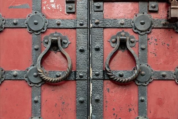 Portões antigos vermelhos com ferragens de metal e maçanetas redondas.
