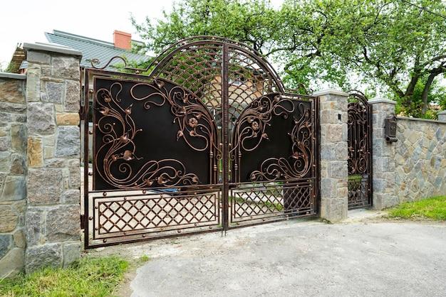 Portões de metal forjados com padrões e um portão em uma cerca de pedra