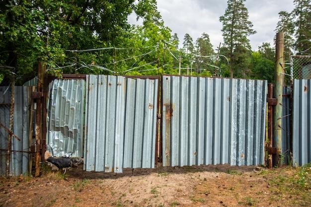 Portões de metal velhos cobertos com arame farpado, propriedade privada bloqueada