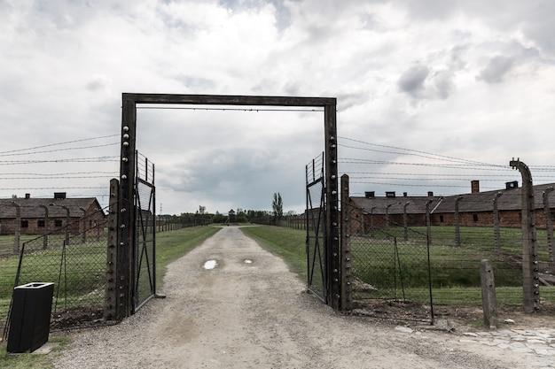 Portões e cerca de arame farpado, campo de concentração alemão auschwitz ii, polônia. Foto Premium