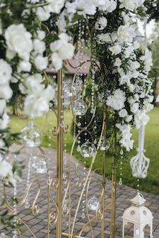 Portões forjados são decorados com flores brancas frescas e vegetação