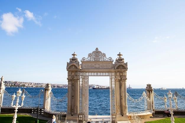 Portões perto do palácio de dolmabahçe levando ao estreito de bósforo com cerca de vidro na frente e a cidade dele em istambul, turquia