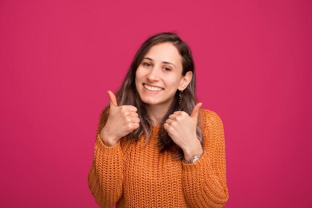 Portraiit de feliz alegre jovem de camisola mostrando os polegares para cima gesto