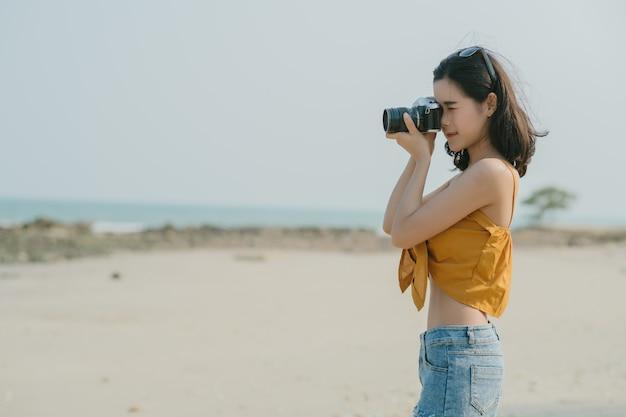 Portrait of asian woman é um fotógrafo profissional com a câmera na praia da tailândia, retrato ao ar livre. jovem fotografia tirando fotos ao ar livre.