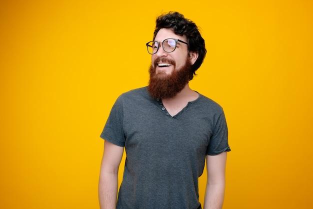 Portraito de smrat alegre com barba, sorrindo e olhando para longe em amarelo