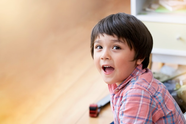 Portraot criança sentada no chão de madeira, relaxando em casa, foco suave de garoto garoto olhando com rosto sorridente enquanto brincava sozinho na sala de jogos. conceito de crianças positivas.