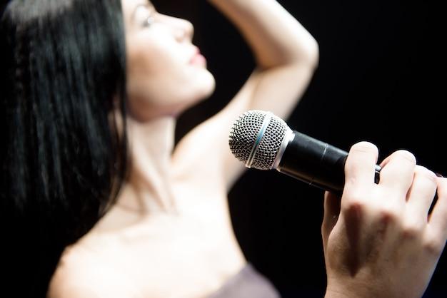 Portret da cantora no clube iluminado.