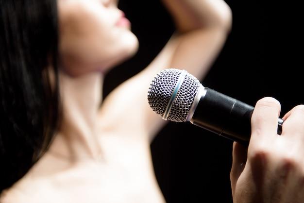 Portret da cantora tocando no clube iluminado.