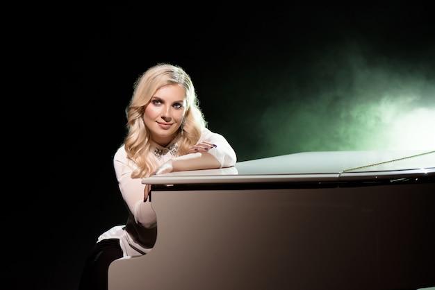 Portret de pianista posando perto de um piano branco no palco sob o feixe de luz.