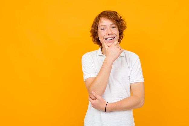 Portret, de, um, ruivo, bonito, sorrindo, pensativo, caucasiano, adolescente, sujeito, em, um, t-shirt branca, ligado, um, amarela, fundo