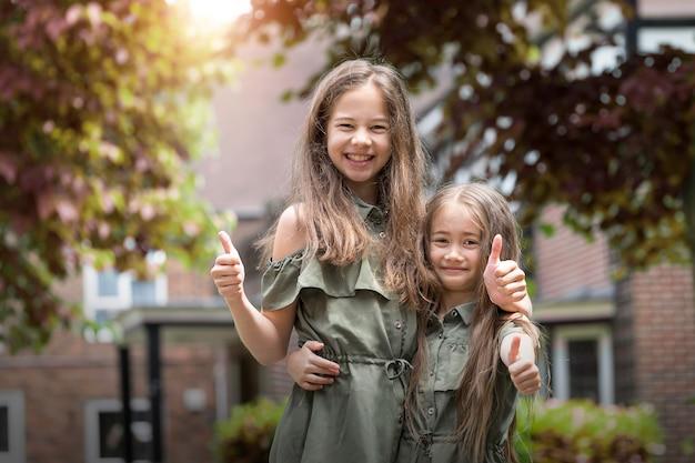 Portret vista frontal de duas irmãs engraçadas com polegares para cima e olhando para a câmera