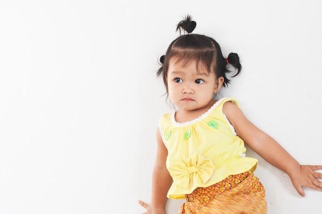 Portriat da menina asiática bonito da criança pequena no vestido tailandês da tradição que está na casa