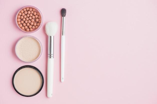 Pós compactos; bronzeando pérolas e pincéis de maquiagem no pano de fundo rosa