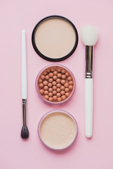 Pós compactos; pérolas bronzeadoras e pincéis de maquiagem na superfície rosa