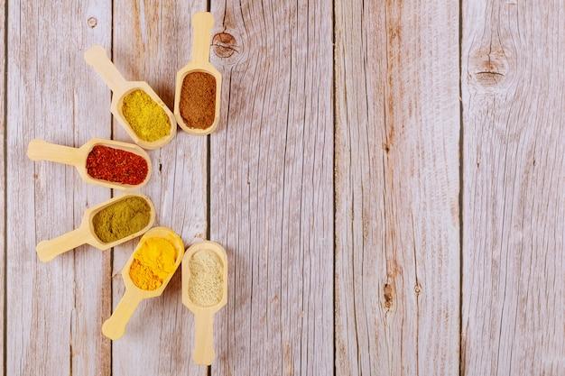 Pós de especiarias à terra coloridas em colheres de madeira na mesa branca