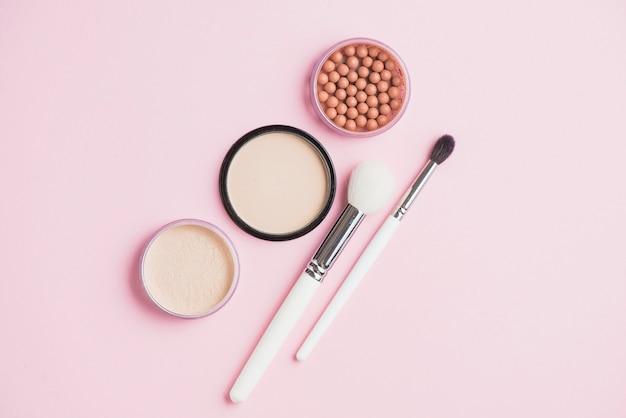 Pós de face; pérolas bronzeadoras e pincéis de maquiagem na superfície rosa