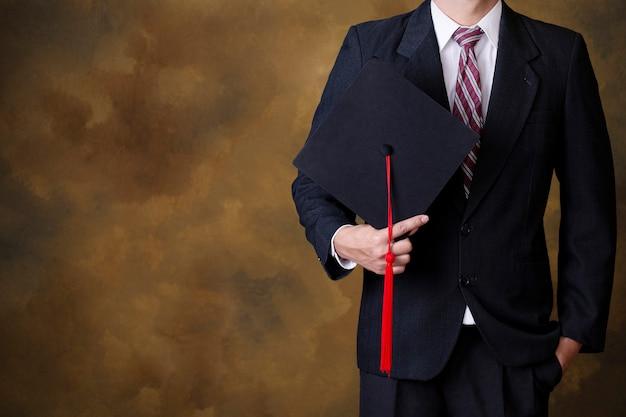 Pós-graduação homem segurando chapéu de formatura preto. copyspace