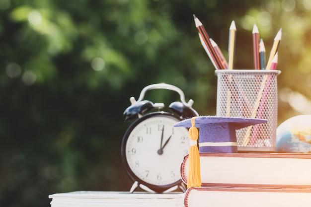Pós-graduação ou educação conhecimento no exterior conceito: graduação cap no livro-texto com caixa de lápis
