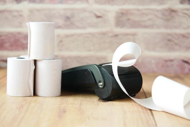 Pos máquina e rolo de papel longo na mesa