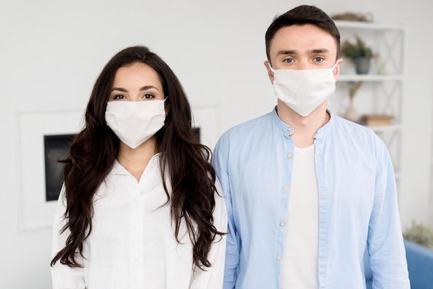 Posando casal em casa com máscaras faciais