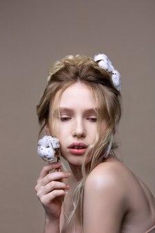 Posando com algodão. jovem modelo com cabelo loiro ondulado posando com um pedaço de algodão nas mãos e no cabelo