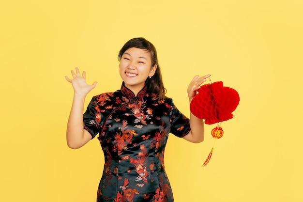 Posando com lanterna, sorrindo, convidativo. feliz ano novo chinês. retrato de jovem asiático em fundo amarelo. copyspace.