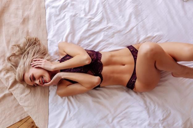 Posando de calcinha. modelo atraente de cabelos loiros e corpo bonito posando com calcinha e sutiã de renda