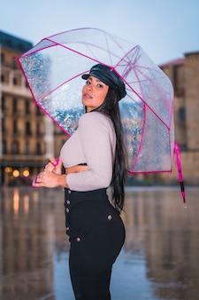 Posando de uma jovem morena latina com um boné de couro na chuva da cidade com um guarda-chuva transparente