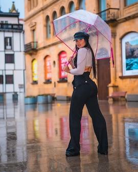 Posando de uma jovem morena latina com um boné de couro na chuva de outono com um guarda-chuva transparente na cidade