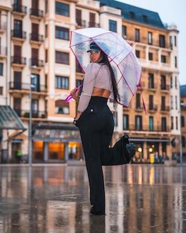 Posando de uma jovem morena latina com um chapéu de couro e calça preta na chuva de outono com um guarda-chuva transparente na cidade