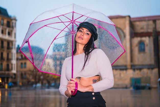 Posando de uma jovem morena latina na chuva da cidade com um guarda-chuva transparente