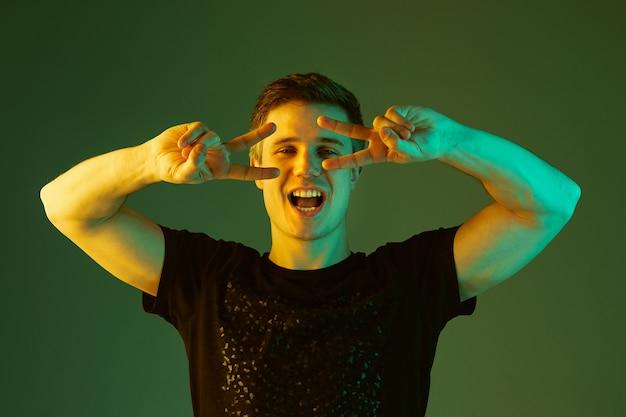 Posando fofo, sorrindo. retrato do homem caucasiano isolado no fundo verde do estúdio em luz de néon. lindo modelo masculino de camisa preta. conceito de emoções humanas, expressão facial, vendas, anúncio.