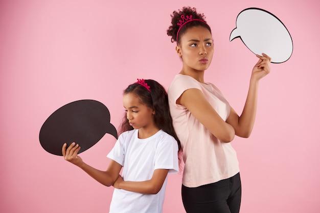 Posando mãe e filha estão segurando balões de fala.