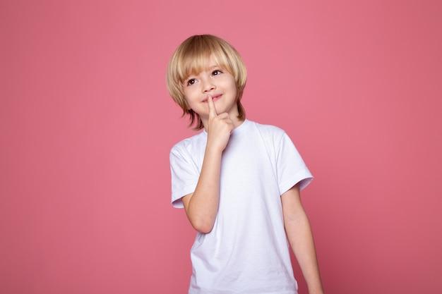Posando menino criança com o dedo nos lábios e parede rosa